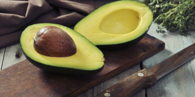 Fresh avocado on cutting board over wooden