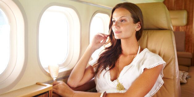 Thoughtful beauty looks out of a planes cabin window while holding champagne appreciatively
