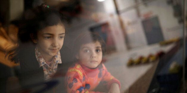 Syrian refugee children from the Abdulwahed family look out to the curling rink as it is reflected in...