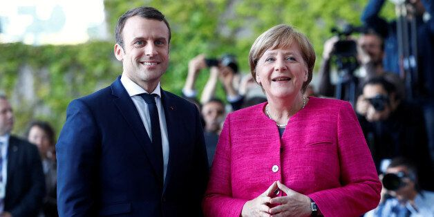 German Chancellor Angela Merkel and French President Emmanuel Macron arrive at a ceremony at the Chancellery...