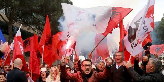 Supporters of the Albanian opposition shout anti-Government slogans as they protest in front of the government...