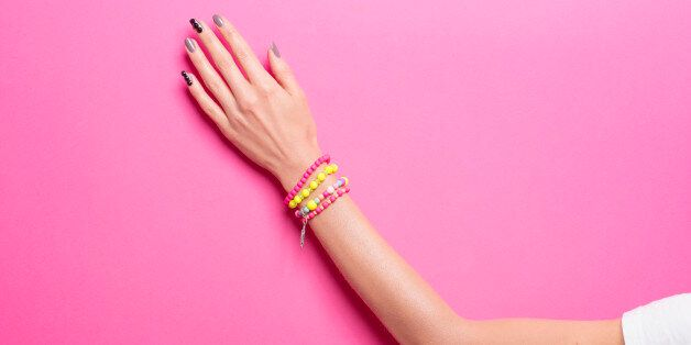 Single woman hand, wearing jewelry, in various background colors. Graphic look, solid bold colors, close...