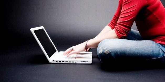 '* Young attractive woman in red tshirt and blue jeans on professional laptop computer, on black