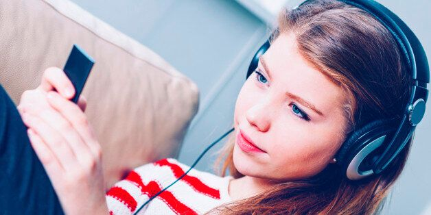 Teenage girl sits in a sofa with a device to play music and podcasts. The item is blurred and could pass...
