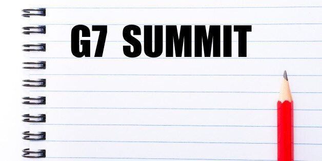 Concept image with words G7 SUMMIT written on notebook page and red pencil on the