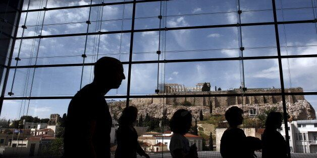 Tourists are silhouetted as they walk inside the Acropolis Museum with the temple of Parthenon on the...