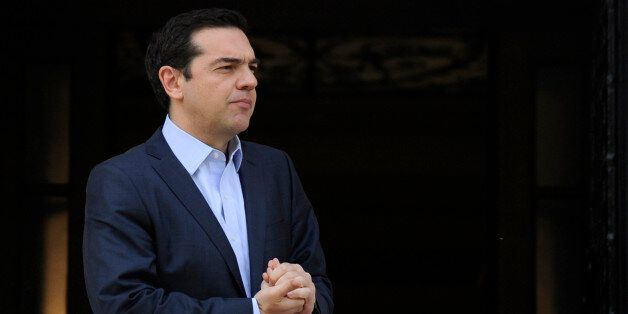 Greek Prime Minister Alexis Tsipras waits to welcome European Council President Donald Tusk at the Maximos...