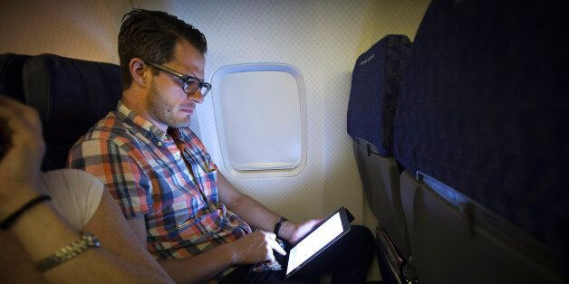A passenger uses a wireless tablet on an American Airlines airplane, which is equipped with Gogo Inflight...