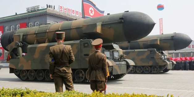 Missiles are driven past the stand with North Korean leader Kim Jong Un and other high ranking officials...