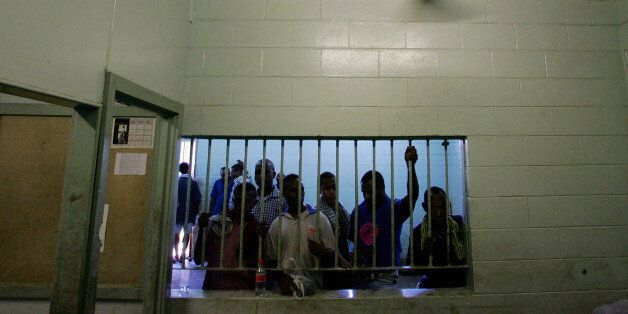 Prisoners look out from behind a cell window as they wait to be processed at the Port Moresby police...