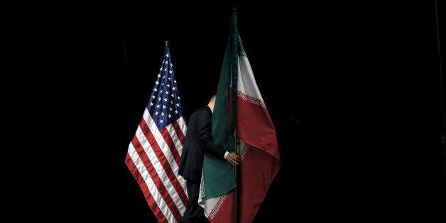 A staff member removes the Iranian flag from the stage after a group picture with foreign ministers and...