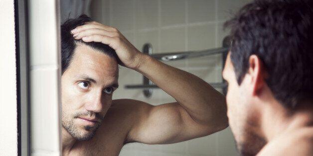 Man checking hair in mirror.
