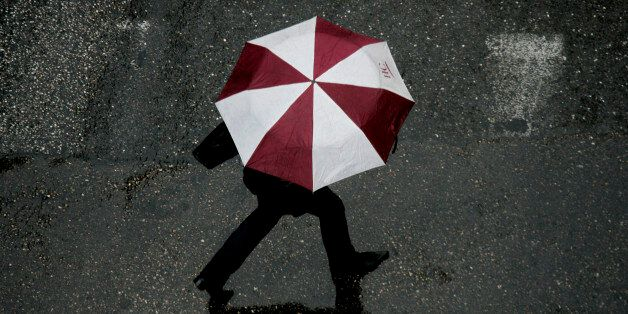 A woman crosses a road, during a long expected rainfall, in central Athens March 22, 2007. Greece has...