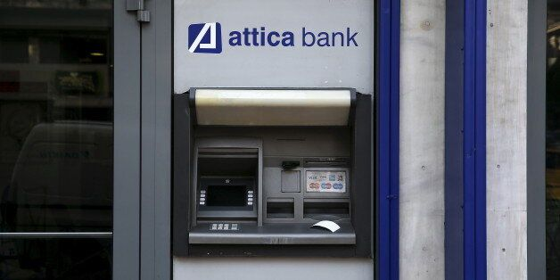 A transaction receipt is seen on an ATM outside a closed Attica Bank branch in Athens, Greece June 30,...