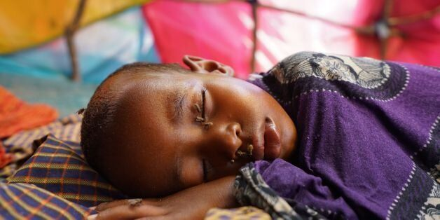 MOGADISHU, SOMALIA - MARCH 7: Covered in flies, a young Somali IDP boy sleeps in the family shelter at...