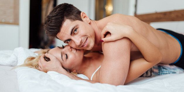 Handsome couple in love in bed being sensual