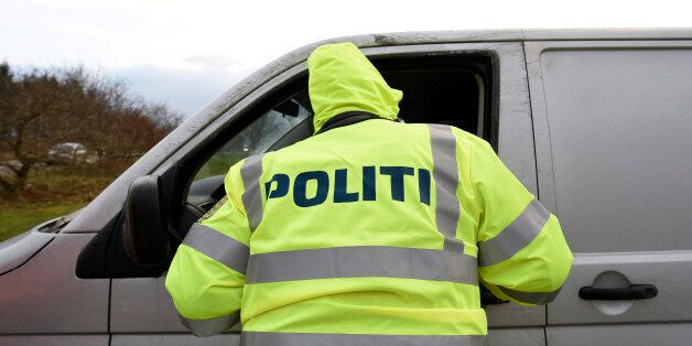 A Danish policeman checks a vehicle at a checkpoint on the German-Danish border crossing in Froslev,...
