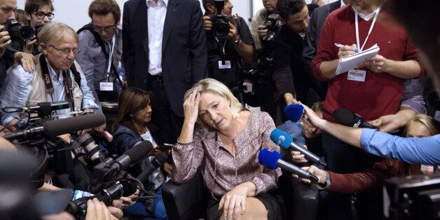 French far-right Front National (FN) party president Marine Le Pen (C) talks to journalists as she attends...