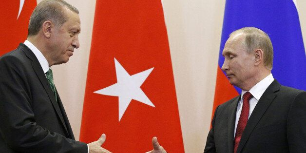 Russian President Vladimir Putin (R) shakes hands with his Turkish counterpart Tayyip Erdogan during...
