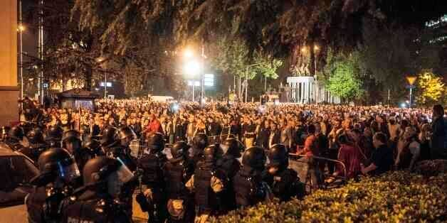 Police face protesters gathered outside Macedonia's parliament after the governing Social Democrats and...