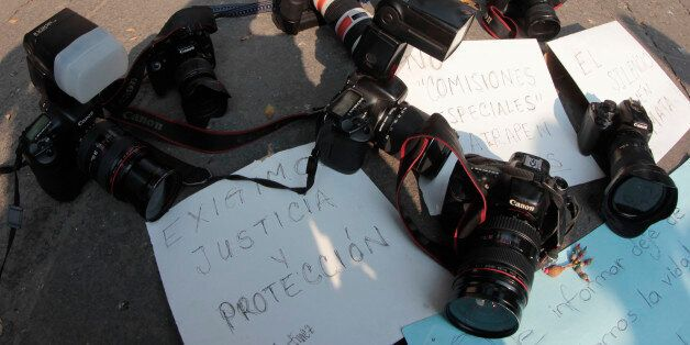 Journalists leave their cameras on posters demanding justice and protection during a protest against...