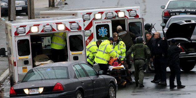 LAWRENCE, MA - APRIL 26: A critically injured woman is placed inside an ambulance during a domestic shooting...