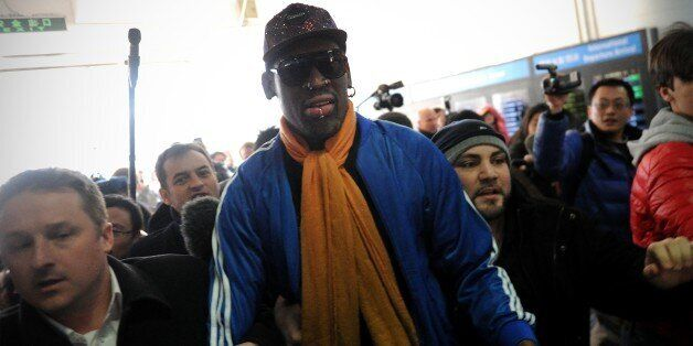 Former US basketball player Dennis Rodman (C) arrives at Beijing International Airport from North Korea...
