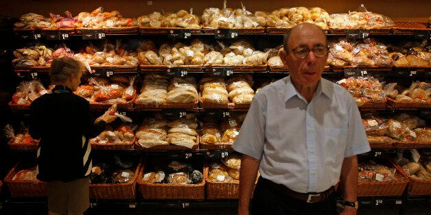A woman buys bread on a supermarket in Lisbon August 30, 2011. Euro zone economic sentiment fell more...