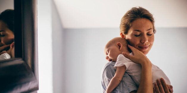 A happy new mother smiles as she craddles her sleeping baby in her arms. She has her eyes closed as she holds her close.