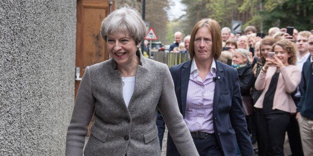 Britain's Prime Minister Theresa May (C) goes door-to-door campaigning for Andrew Bowie, Conservative...