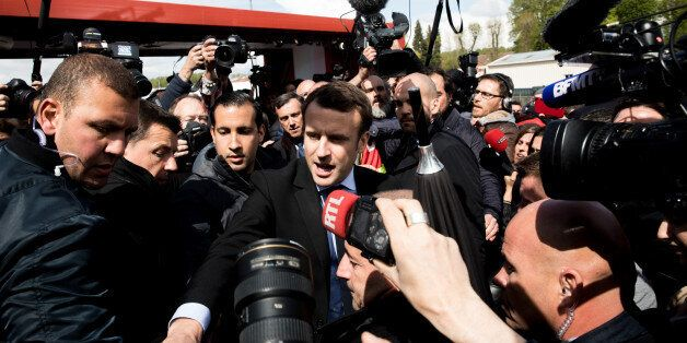 Emmanuel Macron, French presidential candidate, center, stands surrounded by journalists outside the...