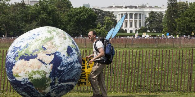 A demonstrator rolls a large globe outside of the White House during the People's Climate Movement March...