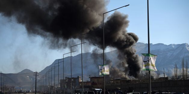 Smoke rises from an Afghan police district headquarters building after a suicide car bomb attack as a...
