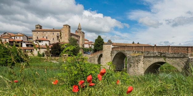 Roman Bridge, people, river, houses and Church of Monastero Bormida in Piedmont,
