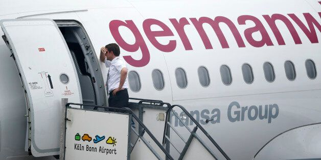A member of staff leans on a Germanwings plane as he waits to depart following a security alert at Cologne...