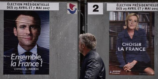 A pedestrian walks past posters of French presidential election candidate for the En Marche ! movement...
