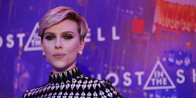 Actress Scarlett Johansson poses as she arrives at a premiere of the