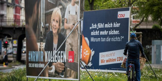 DUESSELDORF, GERMANY - MAY 03: A man rides a bicycle past election campaign billboards of the German...
