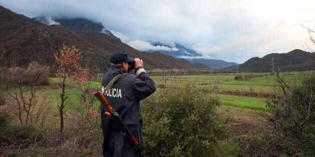 An Albanian police officer patrols at the Albanian-Greek border in Carshove near the city of Permet on...