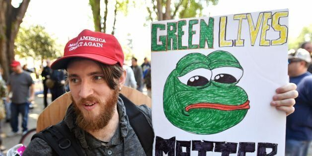 Andrew Knight holds a sign of Pepe the frog, a conservative icon, during a rally in Berkeley, California...