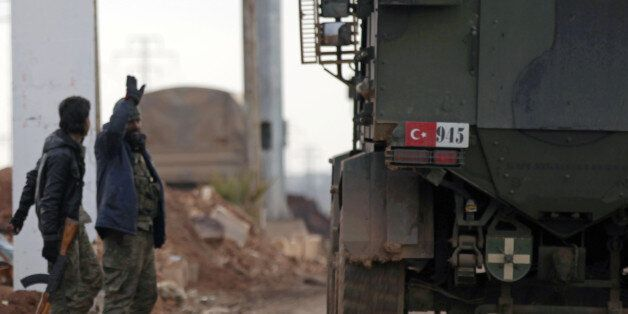 Free Syrian Army fighters gesture as Turkish military vehicles drive in the Syrian rebel-held town of...