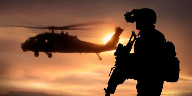 Combat ready special operation forces soldier in an Afghanistan war scene with a black hawk