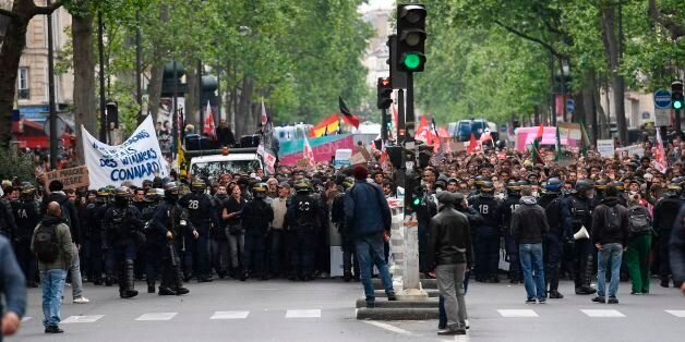 Riot police officers block a street while people take part in a demonstration called by the collectif...
