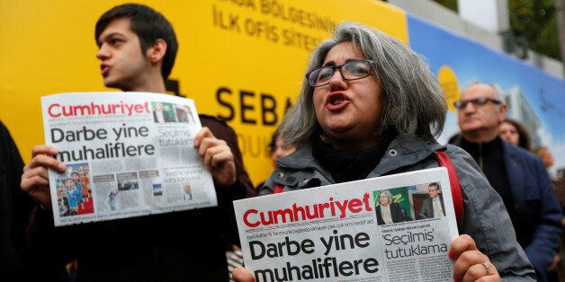Supporters of Cumhuriyet newspaper, an opposition secularist daily, hold today's copies during a protest...