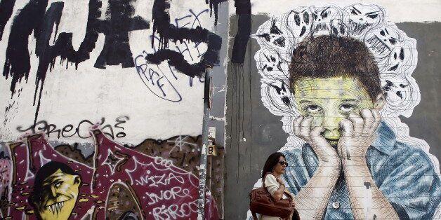 A pedestrian walks past a graffiti in central Athens, April 26, 2015. REUTERS/Kostas
