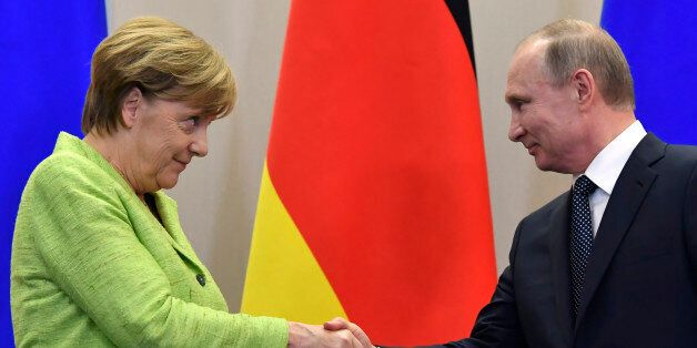 Russian President Vladimir Putin shakes hands with German Chancellor Angela Merkel after a press conference...