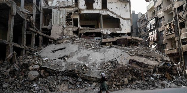 TOPSHOT - Syrian girls walk past destroyed buildings in the rebel-held town of Douma, on the eastern...