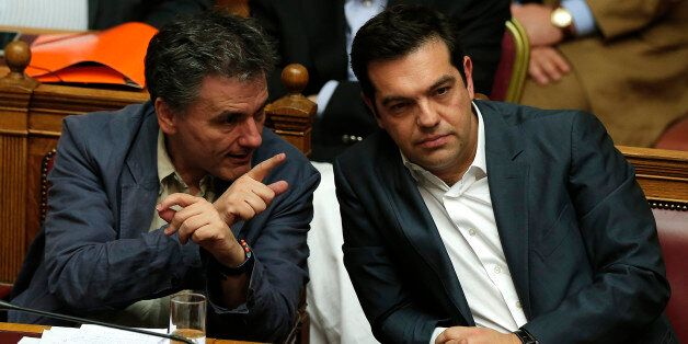 Greek Prime Minister Alexis Tsipras (R) sits next to Finance Minister Euclid Tsakalotos (L) as he attends...