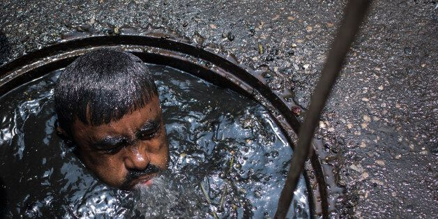 DHAKA, BANGLADESH - MAY 03 : A sewer cleaner of Dhaka City Corporation cleaning out the city's sewers...