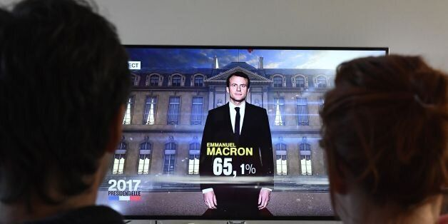 A couple watch a TV screen displaying French President elected Emmanuel Macron with an estimated score...